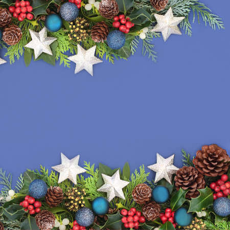 Christmas background border composition with star & blue ball baubles, holly & winter greenery. Xmas composition for the festive season. Flat lay, top view, copy space. Zdjęcie Seryjne