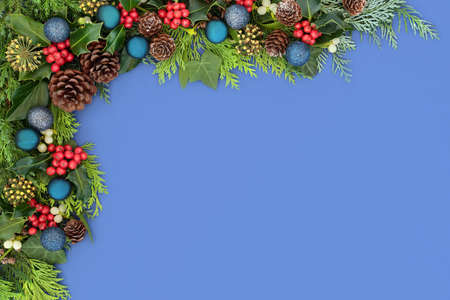 Festive Christmas background border with bauble decorations & traditional winter greenery of holly, ivy, mistletoe, juniper and cedar cypress leaves. Flat lay on blue with copy space.