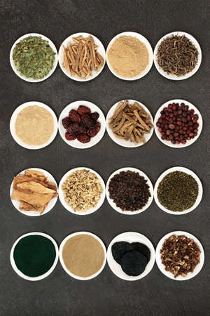Herbs for energy, vitality & fitness used in natural alternative & chinese herbal medicine. In white porcelain bowls on grunge background.