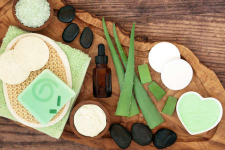 Skincare beauty treatment aloe vera and cosmetic and spa products on olive wood and oak. Soothes sunburn, has anti inflammatory properties, heals skin infections & wounds. Flat lay on rustic wood.