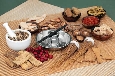 Chinese herbal medicine selection and moxa stick used in moxibustion therapy with mortar and pestle on bamboo mat and mottled green background.