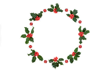 Christmas, winter & New Year holly berry wreath decoration with red bells on white background. Flat lay top view, copy space. Design element.