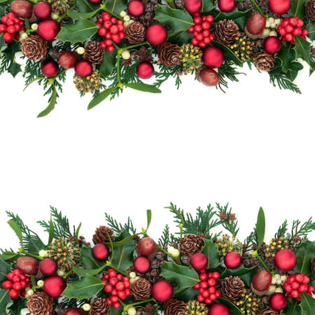 Christmas border with red bauble decorations, holly, mistletoe, ivy, acorns & cedar cypress on white background. Xmas & New Year festive composition. Flat lay, top view, copy space.