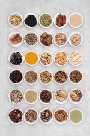 Large collection of Chinese fundamental herbs regularly used in herbal medicine, in porcelain bowls on grunge background. Flat lay.
