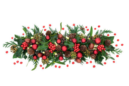 Christmas decorative display for the festive season with red bauble decorations holly & loose berries, mistletoe, acorns & cedar cypress on white background. Xmas and New Year theme. Flat lay, top view.