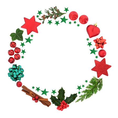 Christmas wreath with holly, winter greenery, red bauble decorations & green stars on white background. Minimal composition for the festive holiday season. Top view, flat lay, copy space. Foto de archivo