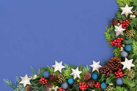 Christmas background border on blue with star & ball baubles, holly & winter greenery of mistletoe, ivy, pine cones & cedar cypress fir. Xmas composition for the festive season. Top view, copy space.
