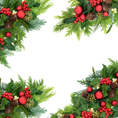 Christmas abstract border for the festive season with red bauble decorations & winter greenery of holly, ivy, mistletoe, cedar cypress & pine cones on white background. Top view, flat lay, copy space.