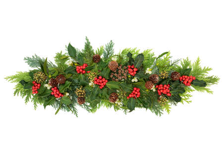 Decorative winter, Christmas & New Year floral composition with holly, ivy, mistletoe, cedar cypress fir leaves & pine cones on white background. Natural decoration for the holiday season. Flat lay.