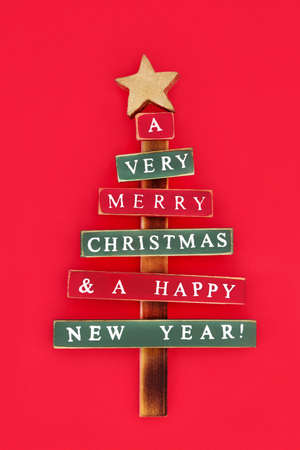 Old fashioned wooden christmas tree with the words Very Merry Christmas & a Happy New Year painted on abstract branches, on red background, symbol for the festive season.