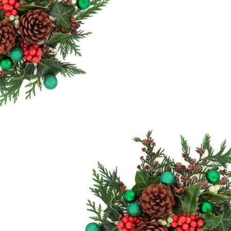 Christmas border with green baubles & winter greenery of holly, mistletoe, ivy, pine cones & cedar cypress fir on white. Xmas & New Year decorative background. Flat lay, top view, copy space.