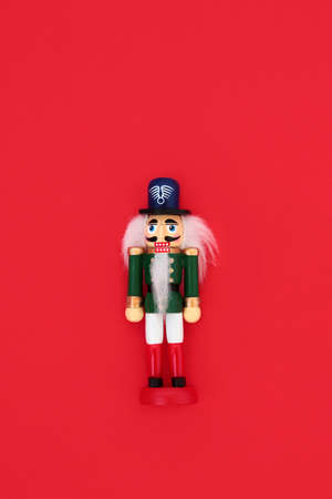 Nutcracker toy soldier figurine on red background. Traditional symbol for the Christmas & holiday season.