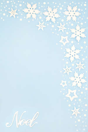 Silver noel sign on pastel blue background border with snowflakes. Festive composition for winter, Christmas & the New Year holiday season. Top view, flat lay, copy space.