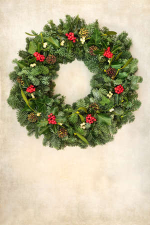 Traditional Christmas spruce fir wreath with winter berry holly, pine cones, & mistletoe on old parchment paper. Natural greenery composition for the festive season & New Year. Copy space.