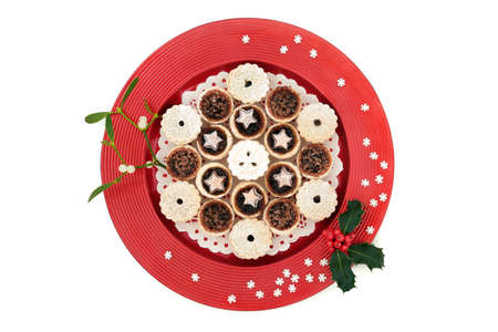 Luxury Christmas mince pies on a red plate with winter berry holly & mistletoe with decorative snowflakes on white background. Xmas food composition for the holiday season.