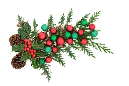 Christmas decoration with holly, cedar cypress, pine cones & red & green baubles on white background. Decorative element for the festive season. Flat lay, top view, copy space. Zdjęcie Seryjne