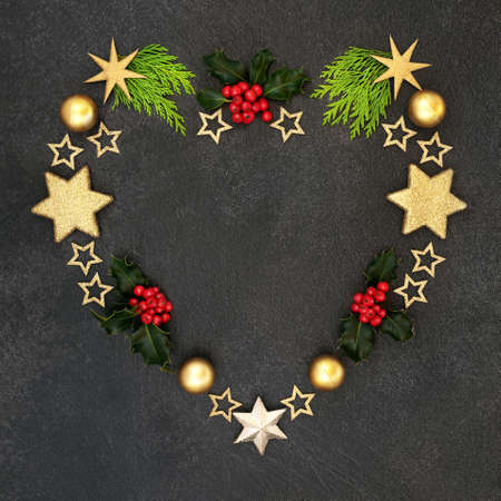 Heart shaped festive Christmas wreath decoration with holly, cedar cypress & gold star decorations on grey grunge background,. Abstract xmas composition for the holiday season.