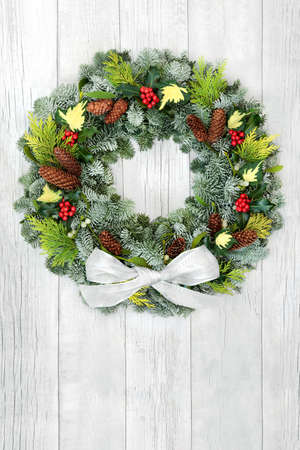 Winter solstice & Christmas  wreath with snow covered fir, cedar, holly, ivy, mistletoe, cedar, pine cones & white bow on rustic wood background. Composition for the xmas holiday season & New Year.