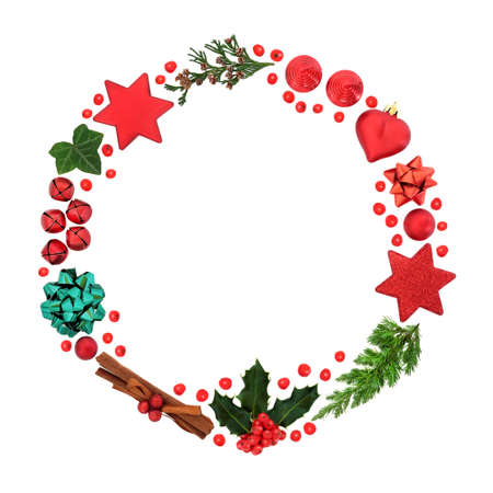 Christmas wreath with holly & loose berries, winter greenery & bauble decorations on white background. Abstract composition for the xmas holiday season. Flat lay, top view, copy space.