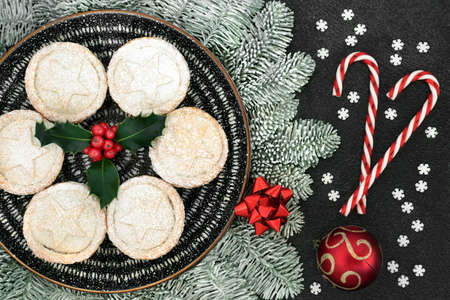Christmas homemade mince pies on a plate with holly, snow covered fir, candy canes snowflake & bauble decorations on grey grunge background. Festive food composition. Flat lay, top view. Zdjęcie Seryjne