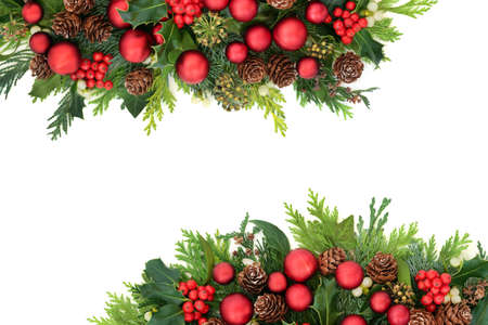 Traditional Christmas border with red baubles & winter flora of holly, ivy, mistletoe, pine cones & cedar cypress fir leaves. Decorative arrangement for the festive season & New Year. Copy space.