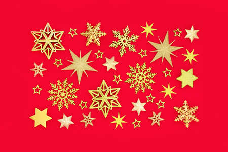 Christmas gold snowflake & star composition on red background. Abstract design for Xmas New Year & holiday season. Flat lay top view. Zdjęcie Seryjne