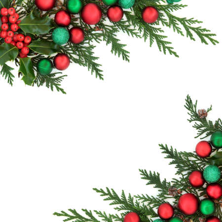 Christmas festive background border with winter holly, cedar cypress & red & green baubles on white background. Decorative composition for the holiday season. Flat lay, top view, copy space.