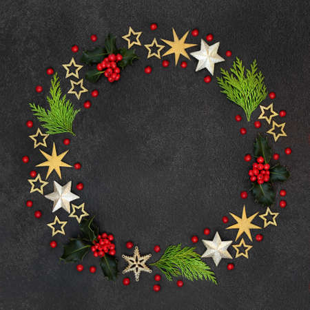 Christmas wreath decoration with winter greenery of holly & loose berries, cedar cypress fir & gold star decorations on grey grunge background. Abstract composition for the xmas & solstice season.