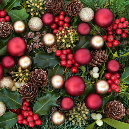 Christmas decorative background composition with red & gold baubles & winter greenery of holly, ivy, mistletoe, cedar cypress leaves & pine cones. Xmas composition for the holiday season. Top view.