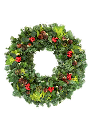 Christmas traditional spruce fir wreath with winter berry holly, ivy, mistletoe, pine cones & acorns on white background. Natural greenery composition for the festive season & New Year. Copy space. Zdjęcie Seryjne