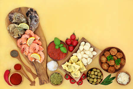 Italian food for a balanced diet low in cholesterol, with seafood, pasta, vegetables, meatballs, cheese & sauces. High in antioxidants, anthocyanins, fibre, omega 3 & protein. On mottled yellow.
