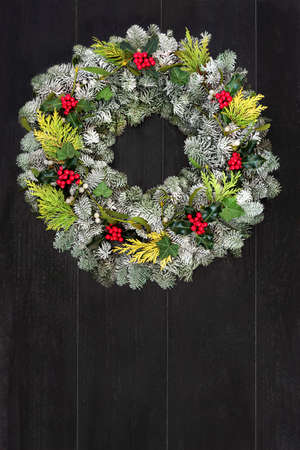 Winter & Christmas wreath with snow covered spruce fir, cedar, holly, mistletoe & ivy leaves on rustic dark wood front door background. Composition for the festive Xmas holiday season & New Year. Zdjęcie Seryjne