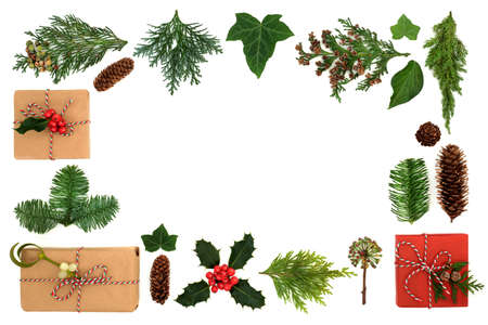Christmas border with eco friendly gift wrapped boxes & winter greenery with holly, firs, ivy & pine cones on white background. Xmas green recycling concept. Flat lay, top view, copy space. Zdjęcie Seryjne