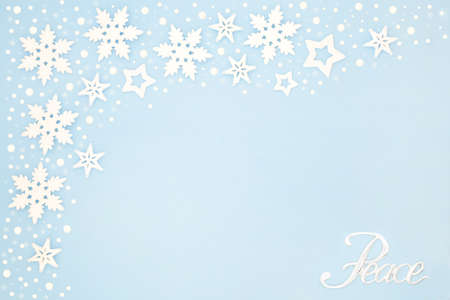 Silver peace sign on pastel blue background border with snowflake decorations. Peace on Earth concept for winter, Christmas & New Year. Top view, flat lay, copy space.
