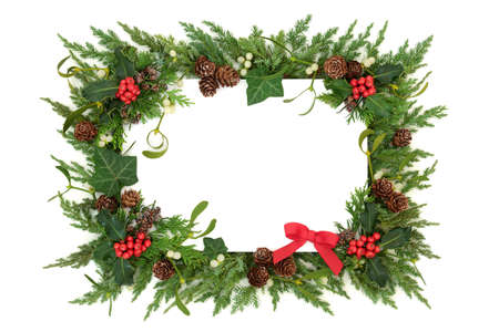 Traditional winter solstice, Christmas & New Year greenery border with small red bow, holly, mistletoe, ivy, cedar cypress & juniper fir on white background. Festive layout. Flat lay, top view, copy space.