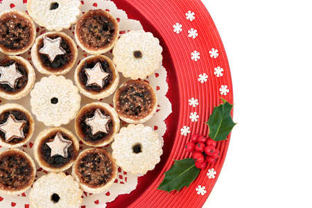 Mini Mince pies for Christmas on a red plate with holly & decorative snowflakes on white background. Xmas food composition for the festive season. Flat lay, top view, copy space.