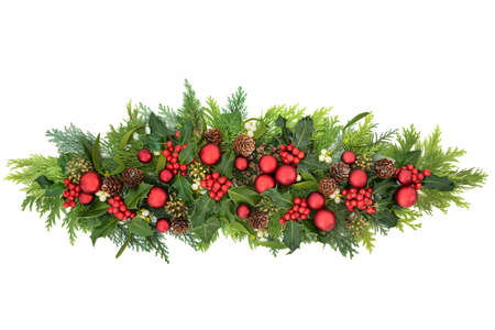 Christmas decoration with red bauble decorations, winter holly with berries, mistletoe, ivy & cedar cypress fir leaves on white background. Decorative display for the festive season. Flat lay, top view, copy space.