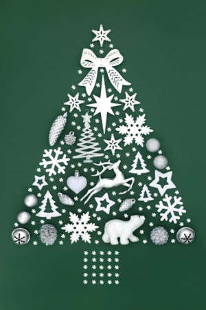 Abstract Christmas tree with decorative snowflakes & white & silver bauble decorations on green background. Festive symbols for the holiday season. Top view, flat lay, copy space..