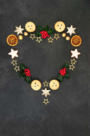 Heart shaped Christmas wreath decoration with winter holly, festive food, gold stars & balls on grey grunge background. Abstract composition for the holiday season.