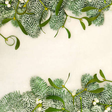 Traditional snow covered fir & mistletoe border on old parchment paper background. Natural winter solstice & Christmas greenery for the festive season and New Year, Top view, flat lay, copy space.