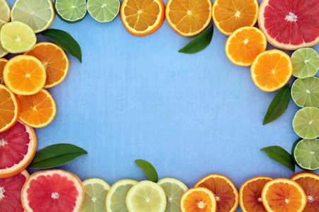 Healthy high fibre citrus fruit border for immune boost with oranges, lemons, limes & grapefruit, high in antioxidants, anthocyanins, lycopene & vitamin c. Natural health care concept on mottled blue.
