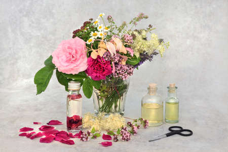 Aromatherapy essential oil preparation with summer herbs & flowers in a vase for infusing in oil. Still life with bottles and scissors on mottled grey background.
