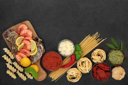 Healthy Italian balanced diet food with foods high in antioxidants, anthocyanins, lycopene, protein, omega 3 and fibre with seafood, pasta, sauces vegetables, herbs & parmesan cheese. Low cholesterol. Zdjęcie Seryjne
