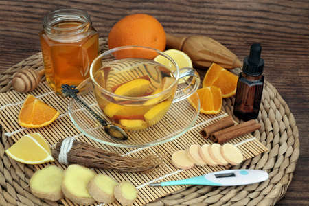 Homemade remedy for cold & flu virus with hot herbal drink with fresh ginger, ginseng, orange, lemon, honey, cinnamon & eucalyptus essential oil with thermometer & vitamin C tablets. Immune boosting. Zdjęcie Seryjne