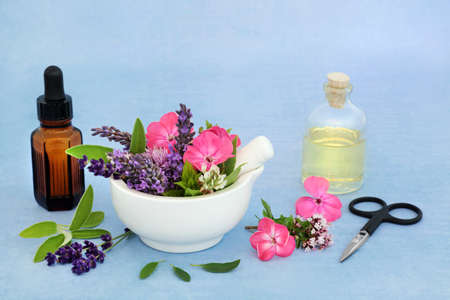 Essential oil preparation for use in aromatherapy & natural herbal medicine with summer flowers, herbs and oil bottles. Naturopathic alternative health care concept. Zdjęcie Seryjne