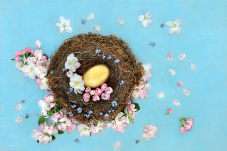 Golden nest egg in a natural birds nest with apple blossom & forget me not flowers and loose on mottled blue background. Savings and Investment concept. Flat lay, top view.