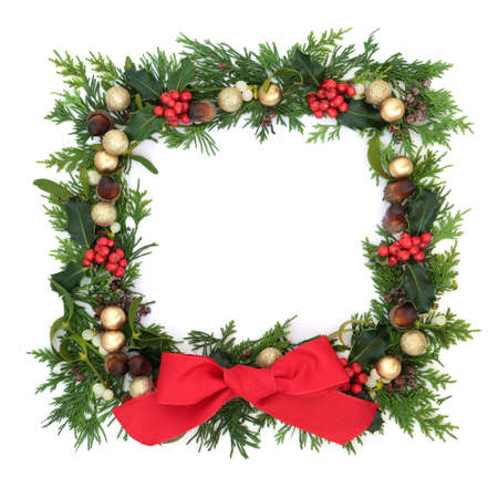 Christmas border decoration on white background with gold baubles & winter greenery of holly, ivy, mistletoe, juniper fir & cedar. Festive  element for the holiday season. Top view, copy space.