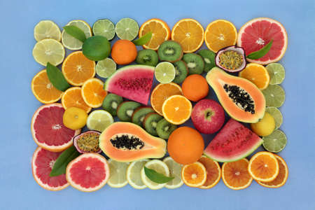 Large collection of high fiber fruit very high in antioxidants, anthocyanins, lycopene vitamin c. Immune boosting health care concept. Flat lay top view with border on mottled blue background.