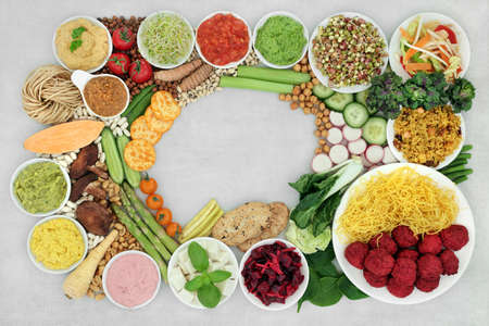 Natural plant based vegan food for a healthy diet with vegetables, tofu, legumes, nuts, dips, salad, grains, snacks and dips. High in protein, omega 3, antioxidants, vitamins, fibre and smart carbs.
