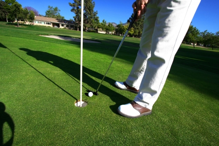putting up: Golfer On Putting Green  Stock Photo